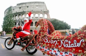"epa00888805 A man dressed as Santa Claus sits on a ""moto-reindeer"" while waving to onlookers as he passes in front of the Colosseum Tuesday 19th December 2006. EPA/CLAUDIO PERI"